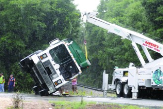 Overturned Waste Pro truck helped to its wheels by The Hulk